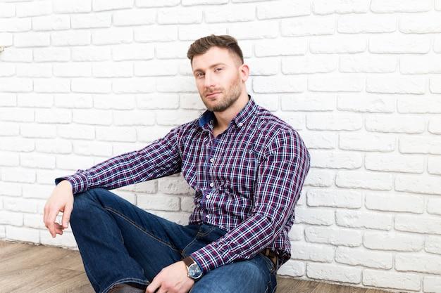 Hombre joven hermoso que sonríe mientras que se sienta en el piso y se inclina en la pared