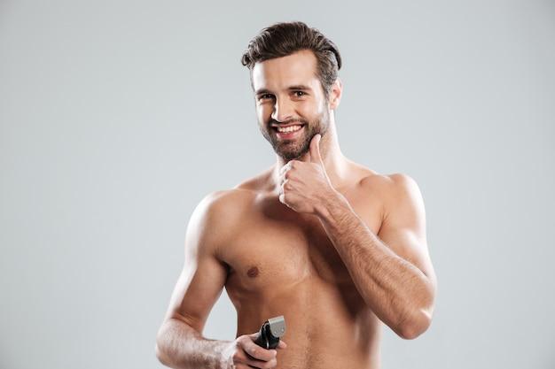Hombre joven hermoso que sostiene la maquinilla de afeitar eléctrica y tocando su barbilla