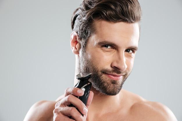 Hombre joven hermoso que sostiene la maquinilla de afeitar eléctrica