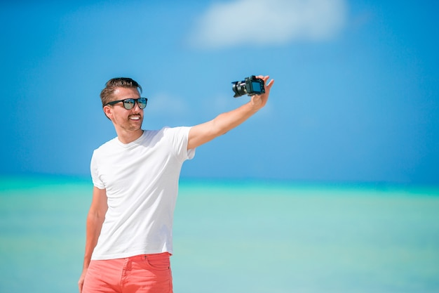 Hombre joven hermoso que toma una foto del uno mismo en la playa tropical