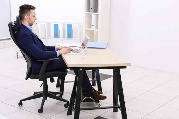 Hombre joven hermoso que trabaja con la computadora portátil en la oficina. concepto de postura incorrecta
