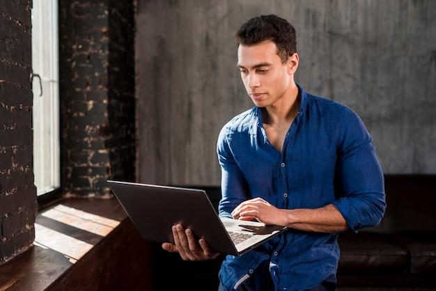 Hombre joven hermoso que usa el ordenador portátil cerca de la ventana