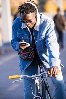 Hombre joven hermoso que usa el teléfono móvil y la bicicleta fija del engranaje en la calle.