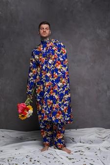 El hombre joven hermoso en la ropa floral que sostiene el gerbera florece en la mano contra la pared gris