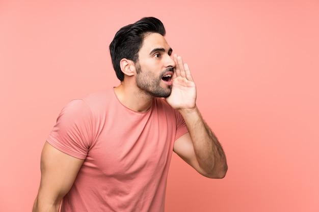 Hombre joven hermoso sobre gritos rosados aislados con la boca abierta de par en par