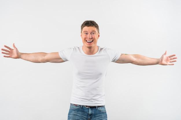 Hombre joven hermoso sonriente outstretching sus brazos aislados en el fondo blanco