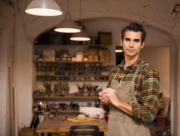 Hombre joven hermoso en el taller de la cerámica que sostiene la arcilla
