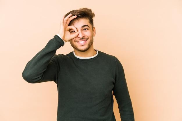 El hombre joven de ian en una pared beige excitó guardar gesto aceptable en ojo.