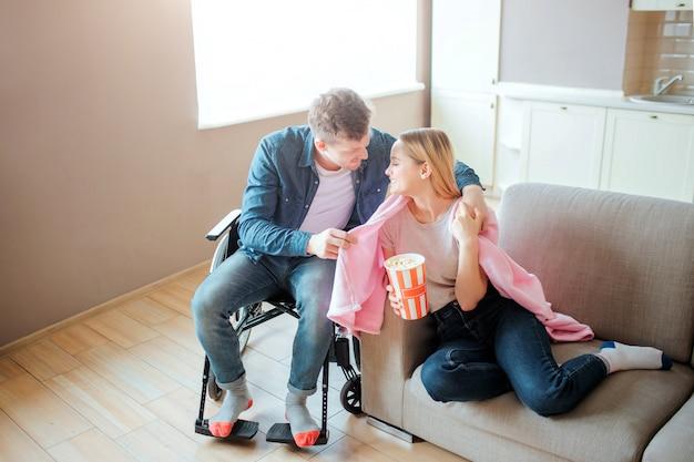 Hombre joven con inclusión cuidar a la novia. él cubre su hombro con una manta y sonríe. persona con necesidades especiales. sentado en silla de ruedas.