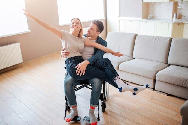 Hombre joven con la inclusión con girlfirend en las rodillas. ella es feliz y llena de alegría. ellos sonrien. persona con necesidades especiales. juntos en una habitación vacía.