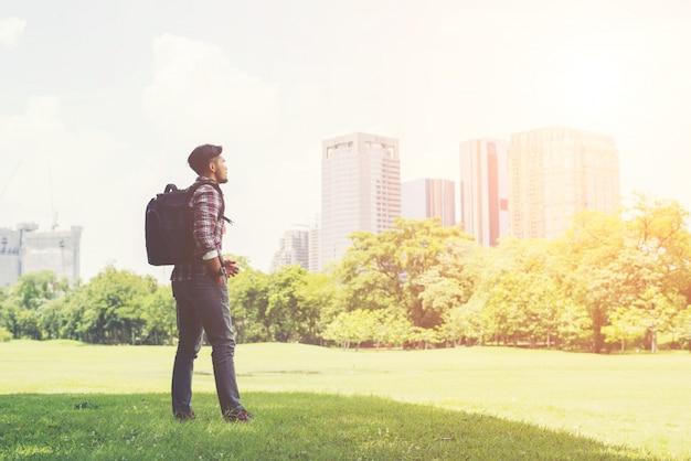 Hombre joven inconformista disfrutar de la ciudad vista desde el parque, antes de ir a tr