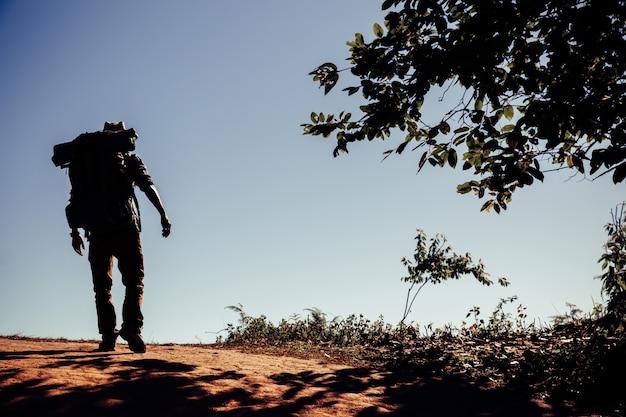 Hombre joven del inconformista con la mochila que disfruta de puesta del sol en la montaña máxima.