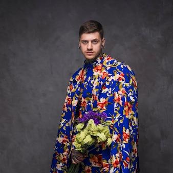 Hombre joven inconformista con orejas perforadas en ropa floral con flores de limonium en la mano