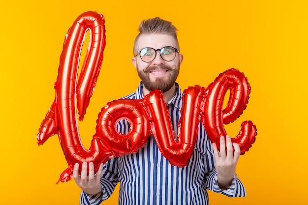 Hombre joven inconformista positivo sosteniendo una inscripción de amor inflable en sus manos sobre una pared amarilla. el concepto de felicitaciones de su alma gemela.