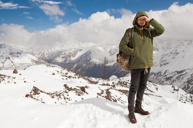 Hombre joven inconformista senderismo en las montañas, viajes de vacaciones de invierno