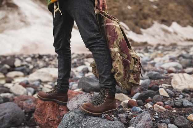 Hombre joven inconformista, senderismo por el río, naturaleza salvaje, vacaciones de invierno, sosteniendo la mochila en las manos, detalles de cerca