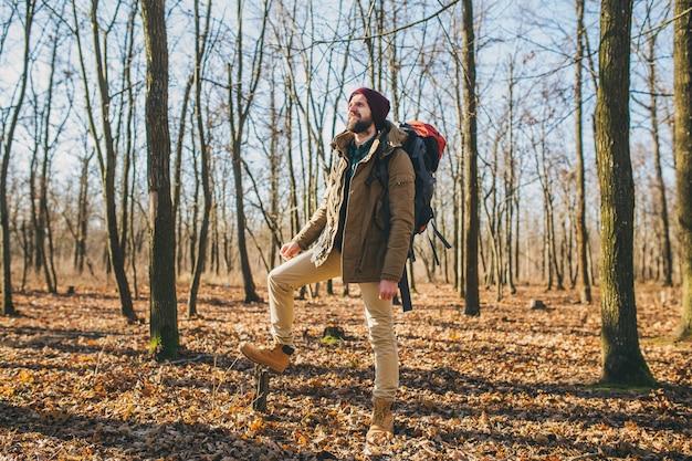 Hombre joven inconformista viajando con mochila en el bosque de otoño con chaqueta y sombrero, turista activo, explorando la naturaleza en la estación fría