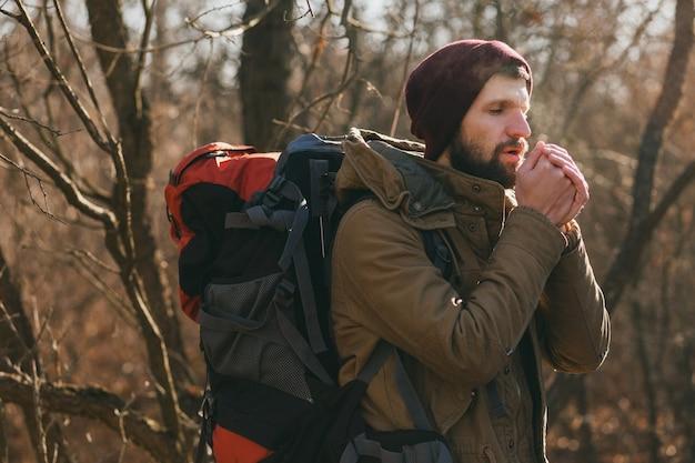 Hombre joven inconformista viajando con mochila en el bosque de otoño vistiendo chaqueta y sombrero
