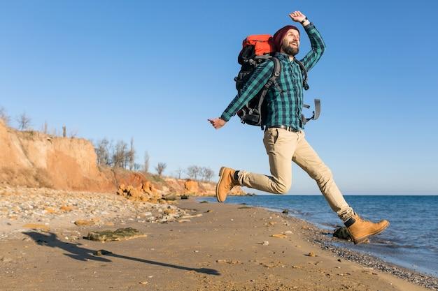 Hombre joven inconformista viajando con mochila en la costa del mar de otoño vistiendo chaqueta y sombrero