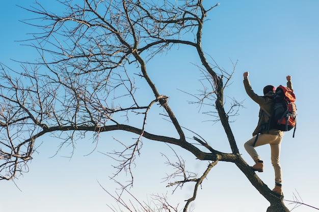 Hombre joven inconformista viajando con mochila, de pie en el árbol contra el cielo, vistiendo chaqueta abrigada, turista activo, explorando la naturaleza en la estación fría
