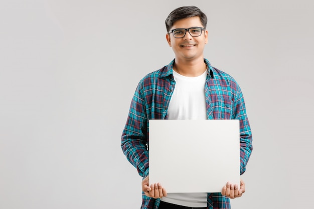 Hombre joven indio, asiático que muestra el letrero en blanco