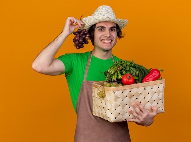 Hombre joven jardinero en delantal y sombrero con caja llena de verduras y racimo de uva mirando con cara feliz sonriendo ampliamente de pie sobre la pared naranja