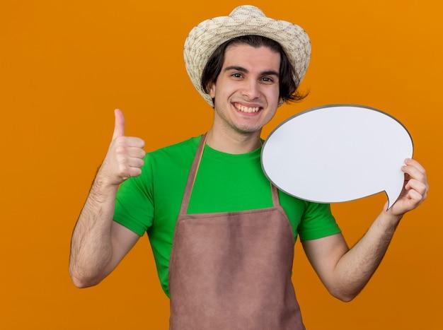 Hombre joven jardinero en delantal y sombrero con cartel de burbujas de discurso en blanco mirando a cámara sonriendo alegremente mostrando los pulgares para arriba sobre fondo naranja