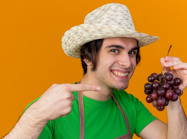 Hombre joven jardinero en delantal y sombrero mostrando racimo de uva apuntando con el dedo índice sonriendo con cara feliz de pie sobre la pared naranja