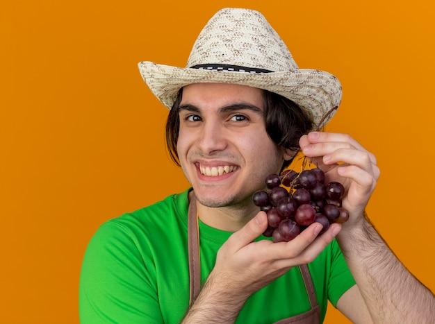 Hombre joven jardinero en delantal y sombrero mostrando racimo de uva mirando sonriendo con cara feliz de pie sobre la pared naranja