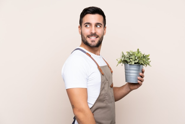 Hombre joven jardinero sobre pared aislada