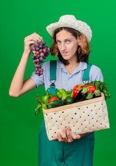 Hombre joven jardinero vestido con mono y sombrero con caja llena de verduras frescas