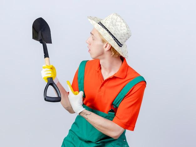 Hombre joven jardinero vestido con mono y sombrero en guantes de goma sosteniendo una pala apuntando con un índice figner mirando confundido