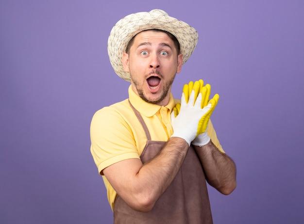 Hombre joven jardinero vestido con mono y sombrero en guantes de trabajo cogidos de la mano juntos mirando asombrado y sorprendido