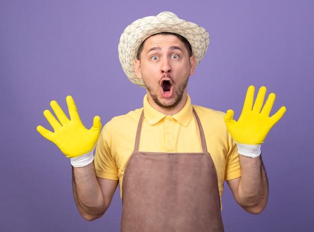 Hombre joven jardinero vestido con mono y sombrero en guantes de trabajo mirando al frente asombrado y sorprendido levantando las manos en rendición de pie sobre la pared púrpura