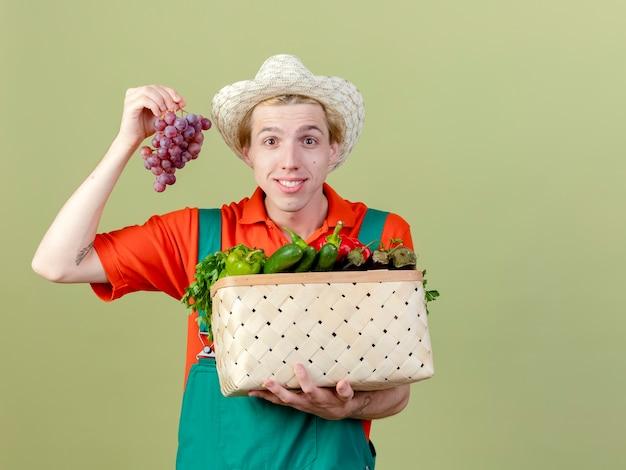 Hombre joven jardinero vestido con mono y sombrero sosteniendo la caja llena de verduras y racimo de uva mirando a la cámara con una sonrisa en la cara de pie sobre fondo claro
