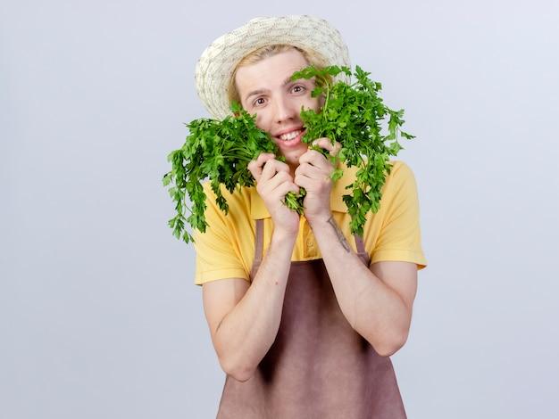 Hombre joven jardinero vestido con mono y sombrero sosteniendo hierbas frescas con una sonrisa en la cara feliz