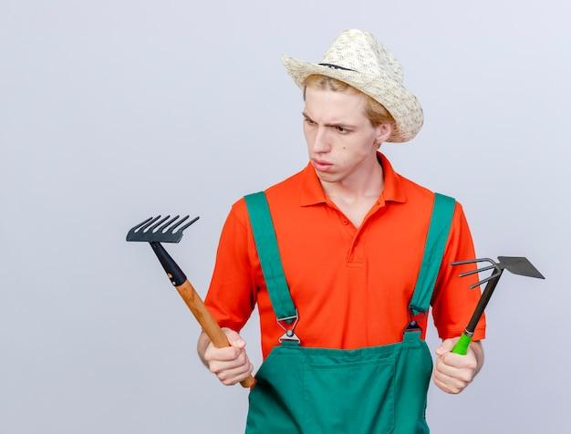 Hombre joven jardinero vestido con mono y sombrero sosteniendo mini rastrillo y azadón mirando confundido e incierto tratando de tomar una decisión de pie sobre fondo blanco