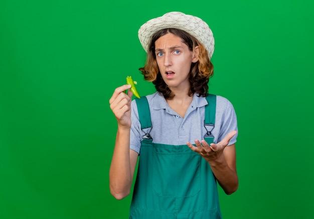 Hombre joven jardinero vestido con mono y sombrero sosteniendo mitades de ají verde