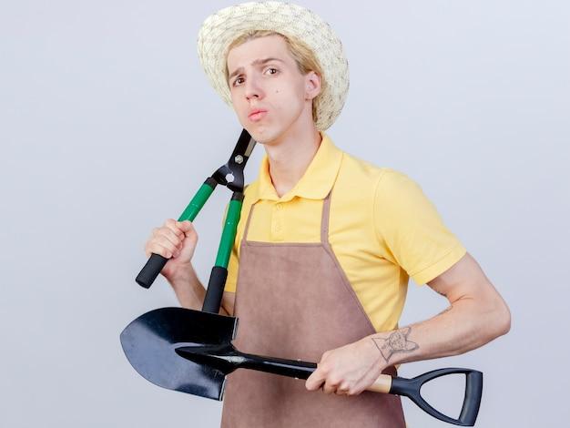Hombre joven jardinero vestido con mono y sombrero sosteniendo pala y cortasetos con cara seria