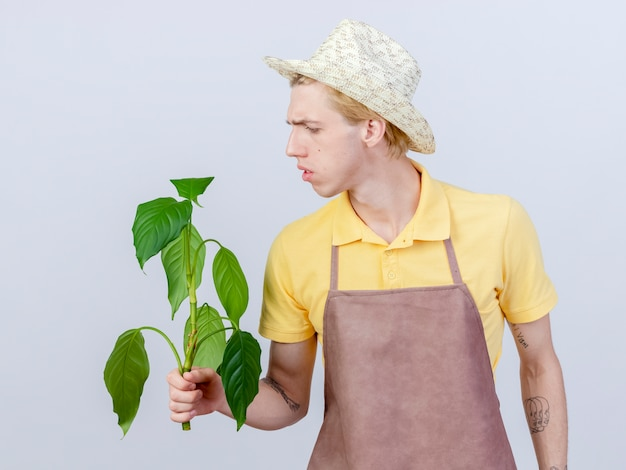 Hombre joven jardinero vestido con mono y sombrero sosteniendo una planta mirando confundido
