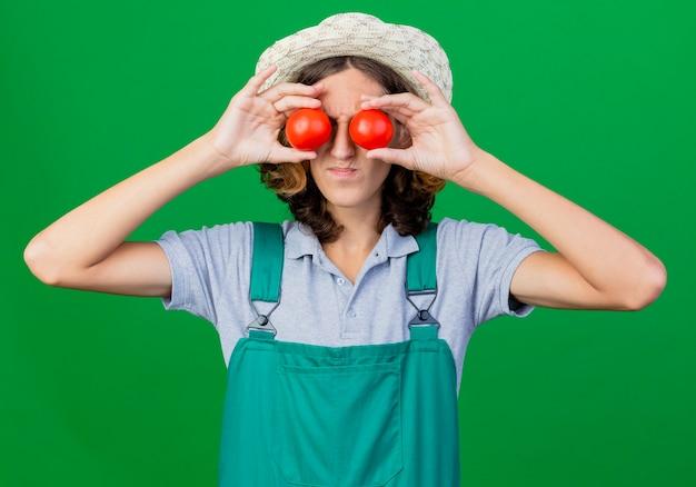 Hombre joven jardinero vestido con mono y sombrero sosteniendo tomates frescos cubriendo los ojos