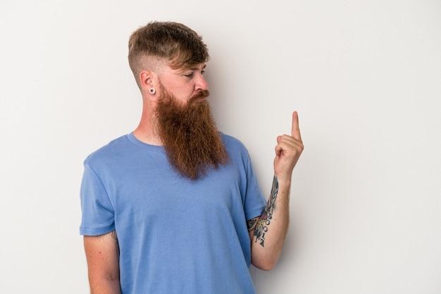 Hombre joven de jengibre caucásico con barba larga aislado sobre fondo blanco apuntando con el dedo como si invitara a acercarse.