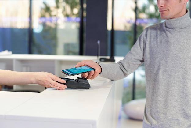 Hombre joven en jersey gris con teléfono inteligente con página de banca en línea en la pantalla durante el proceso de pago sin contacto en la tienda o centro de ocio