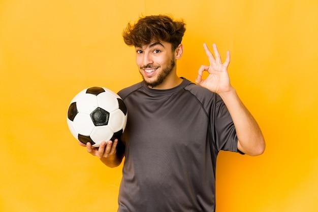 Hombre joven jugador de fútbol alegre y confiado mostrando gesto ok