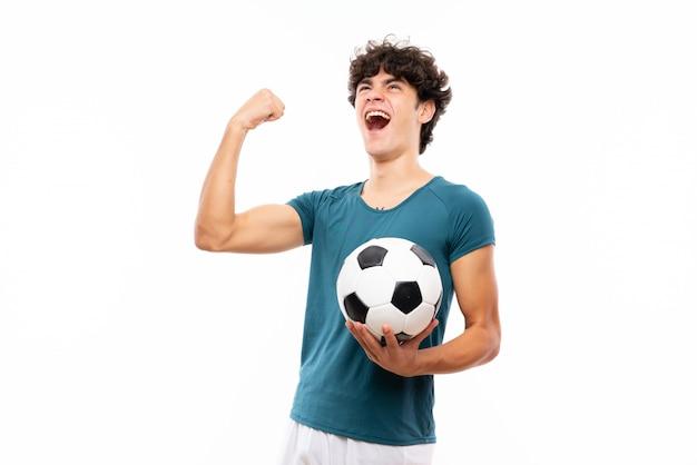 Hombre joven jugador de fútbol sobre pared blanca aislada