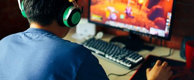 Hombre joven jugando juego en computadora, banner