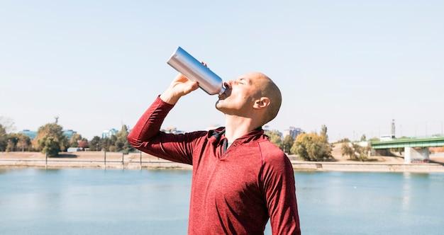 Hombre joven juguetón el agua potable de la botella que se coloca cerca del lago