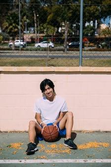 Hombre joven juguetón que se sienta en el asfalto con baloncesto al aire libre