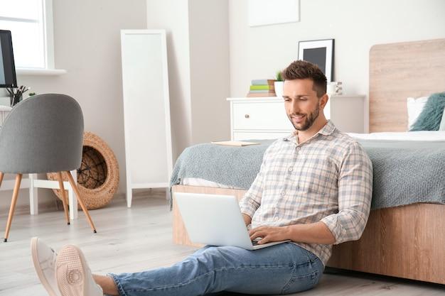 Hombre joven con laptop trabajando en casa