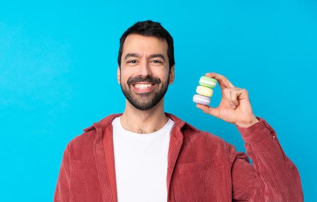 Hombre joven con macarons sobre pared aislada